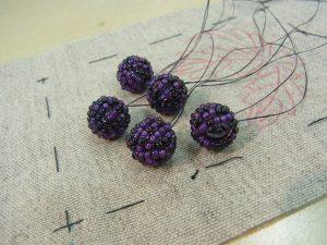 パールの周りにビーズを巻いた葡萄の実があります。