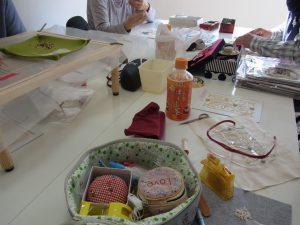 皆んなでテーブルを囲んでビーズ刺繍をしています。