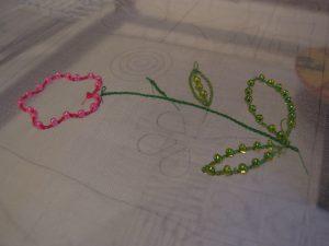 5枚の花びらと葉が刺してあります。ところどころにビーズが光っています。