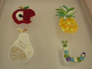りんご、洋梨、パイナップル、芋虫が刺繍されています。