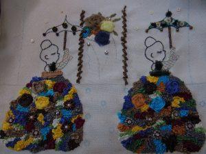 お花のドレスを着たご婦人が二人並んでいます。刺しているパコ型の傘も花でいっぱいです。