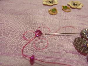 糸が出ている右隣の印に針を入れて、スパンコールの際に針を戻します。