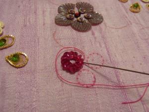 刺したスパンコールの周りを、糸で一周したら針を裏側に落として玉止めをします。