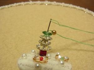 メタルビーズと花形ビーズの間に針を入れてボードの下まで針を通します。