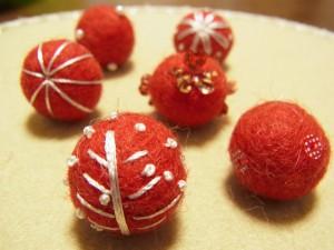 羊毛玉に糸で木や、お花などの模様を刺繍しています。