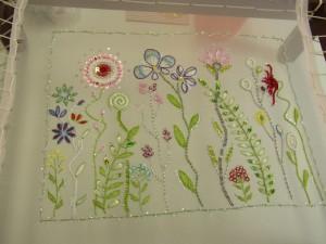 カラフルなお花が沢山刺してあります。茎のジグザグや、花や葉のサテンステッチが沢山刺してあります。