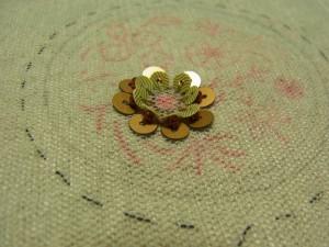 ビーズをスパンコールで挟んで一緒に刺してあります。円形のお花が完成しています。