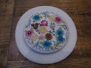 スパンコールやリボンで刺した花が沢山あります。円形の壁掛けです。