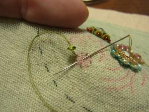 8等分になっている円から針を出し、中心に針を入れます。再び外側の円の等分の印がある位置に針を出します。
