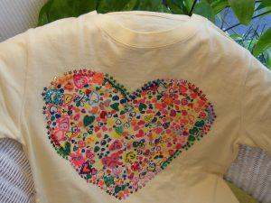 Tシャツにカラフルなハートの模様があります。星型のキラキラスパンコールがピッタリ合っています。