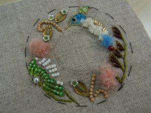 円形の中に鳥と花が刺してあります。オーガンジーリボンで作った花もあります。