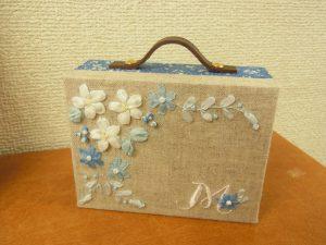 リボン刺繍で花が刺してある、トランク型の糸を入れるケースです。