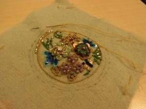 円形のチャームです。花や蜂、蝶々の周りをワイヤーと竹ビーズで囲っています。
