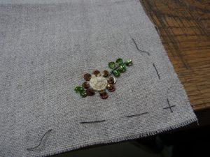 中心に隙間がなく綺麗に巻かれてた花があります。周りにスパンコールが刺してあります。