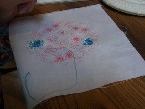 スパンコールで同心円の花を刺しています。