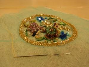 円形のチャームの刺繍が完成しています。花、蜂、蝶々が刺してあります。