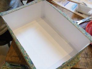 長方形の箱を組み立てて、周りに生地を貼っています。