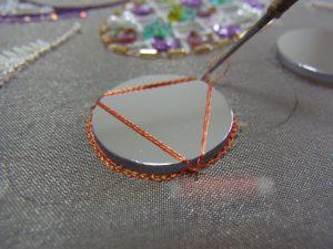 円形ミラーの周りにチェーンステッチをします。糸を正三角形に渡しながらミラーを固定しています。