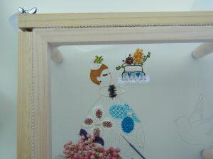 いちごの帽子をかぶり、花模様のドレスを着た女性がケーキを持っています。