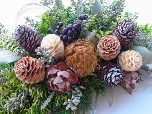 木の実や松ぼっくりなどでクリスマスリースができています。