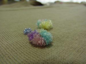 ニットセーターの胸元に、オーガンジーリボンで作った花を刺しています。