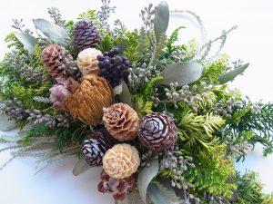 杉の葉に松ぼっくりと木の実を飾ったクリスマスリースです。