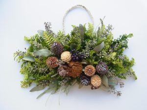 横長のクリスマスリースです。松ぼっくりや木の実が飾ってあります。