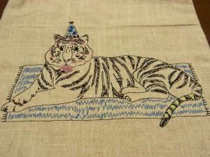 刺繍でできているトラが、マットの上に横たわっています。