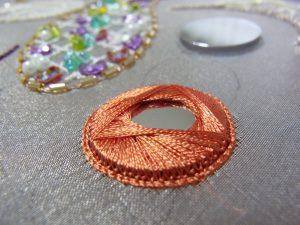 円形ミラーが糸で固定されています。表面は正三角形の模様ができています。