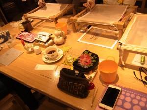大きなテーブルで皆んなでビーズ刺繍をしています。