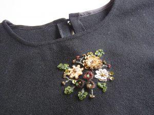 お洋服の首元にスパンコールのお花が刺してあります。
