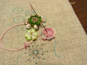円形の花を刺しています。外側から針を出し中心に落とします。