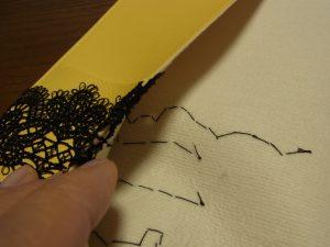 カバーの裏面に縫い止めた糸が渡っています。
