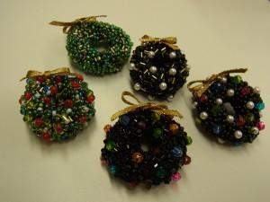 クリスマスリースのブローチが5個あります。金のリボンが飾ってありそれぞれ異なった色で出来ています。