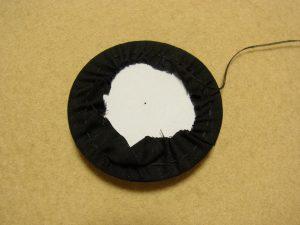 生地でボードを覆っています。糸を引きながら綺麗な円形にしていきます。
