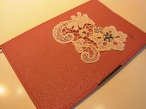 手帳の表紙に花の形の綿ブレイドを刺していきます。