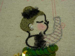 髪はレーヨン糸で、手袋はメタル糸を使って刺しています。