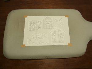 アイロン台の上に図案用紙があります。四隅をガムテープで止めます。