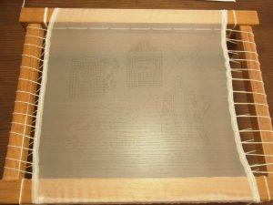 長方形の木枠に、図案を転写した生地が張ってあります。