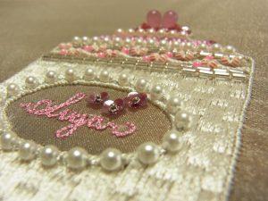 楕円形の中に英字が刺繍されています。周りは市松模様の刺繍がありパールが飾ってあります。