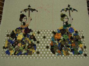 二人の女性が花のドレスを着て傘を刺しています。亀甲模様が周りに刺してあります。