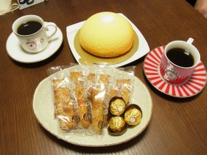 コーヒーとチーズケーキ、お煎餅、チョコレートが並んでいます。
