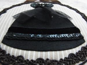 黒いドレスが刺繍されている円形の壁飾りです。
