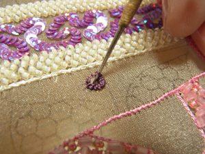 穴に針を入れ 糸を引き抜き円形に刺した糸の外側に針を落とします。