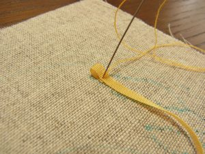 折り返したリボンを糸で止めます。