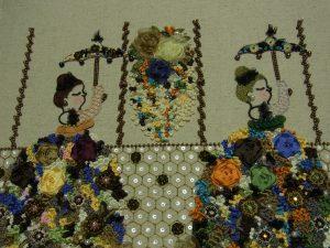 2人の女性の間にリボン刺繍した花があります。両端に縦方向にビーズが刺してあります。