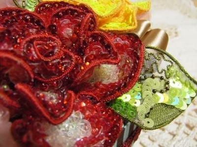 丸小ビーズを花びらの先端に刺した赤い花と、美しくデザインされた葉。