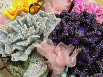 丸箱の蓋にアリワーク(インドに昔から伝わるビーズ刺繍の技法)で刺繍した5種類の色鮮やかな花が、隙間なく飾ってあります。所々にリボンで作った花もあります。