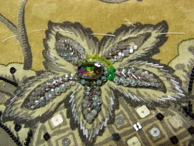 がまぐちタイプのバック。大きい花の中心にオールラに輝く大きいストーンを刺し、その周りにビーズ、スパンコール、モールを使って刺繍をしています。