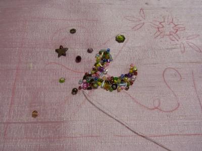 ピンクのインドシルクの生地に、イニシャルのyを50種類のビーズとスパンコールを使って刺し埋めています。